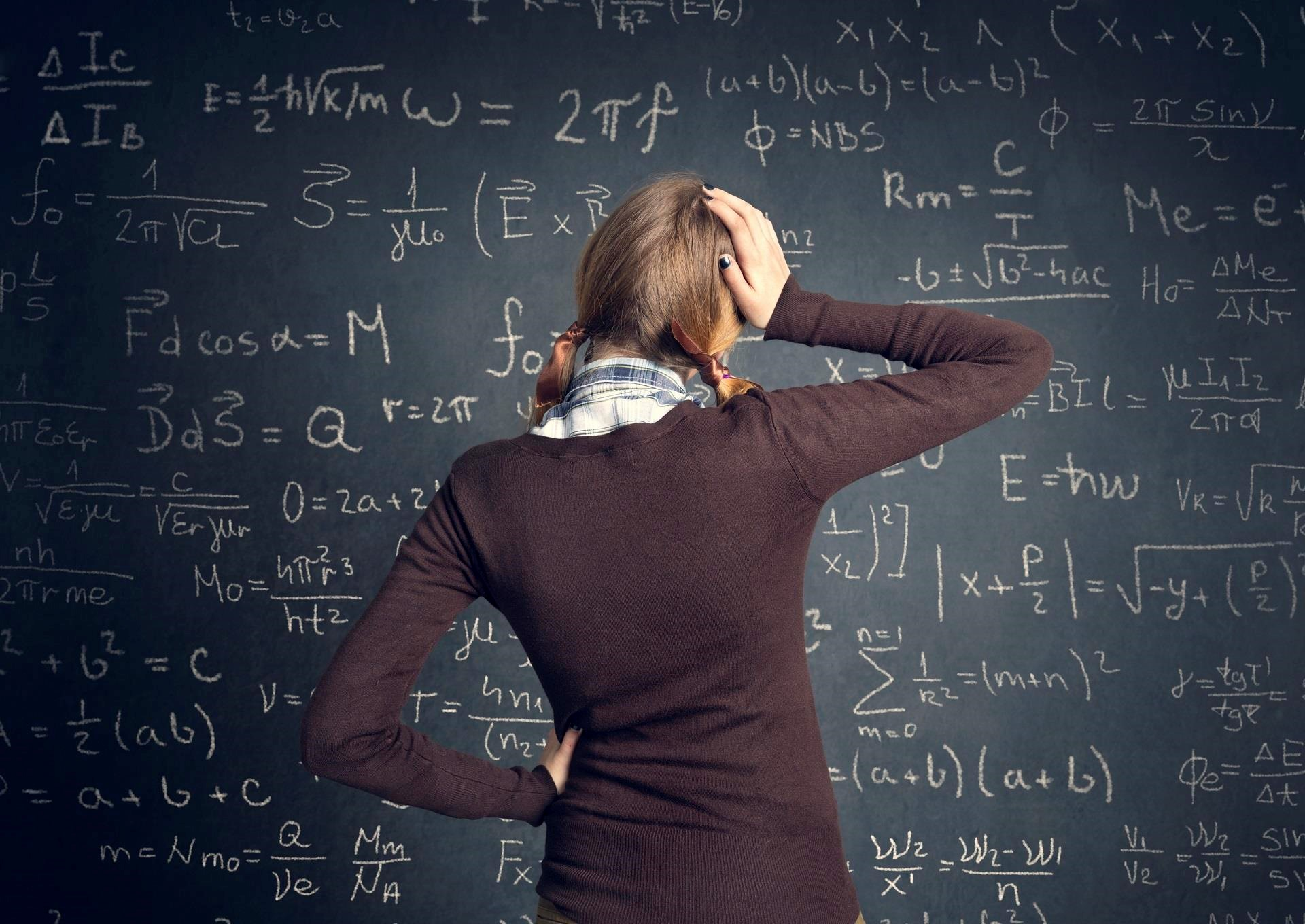 Woman looking at complex formulae on a blackboard