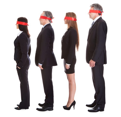 Four businessmen and women queuing with blindfolds on